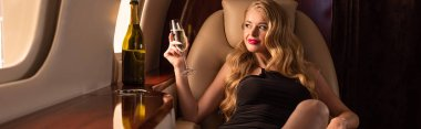 beautiful blonde woman with champagne sitting in plane