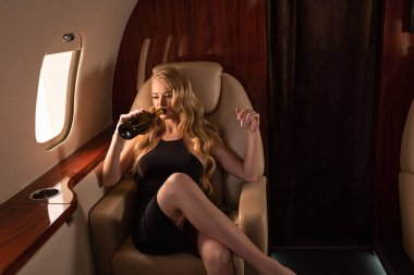 attractive blonde woman with champagne sitting in plane
