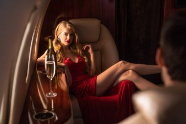 selective focus of sexy woman in red dress flirting with man in airplane