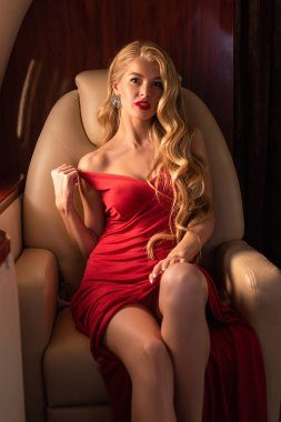 sexy blonde woman in red dress sitting in plane