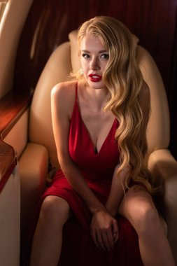 passionate glamorous woman in red dress sitting in plane