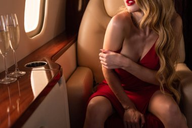cropped view of sexy girl with champagne sitting in plane