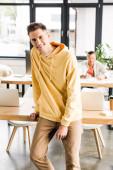 fiatal mosolygós üzletember néz kamera, miközben áll a munkahelyen az irodában
