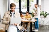 mladý podnikatel pomocí notebooku v blízkosti multikulturní kolegové pracující v úřadu