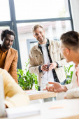 Photo selective focus of multicultural businesspeople discussing startup project in office