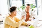 dva mladí podnikatelé si potřásají rukama, když spolu sedí na pracovišti