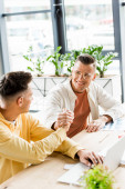 two young, handsome businessmen shaking hands while sitting together at workplace