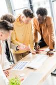 čtyři multikulturní podnikatelé analyzující dokumenty s grafy a grafy při společné práci na zahajovacím projektu v kanceláři