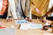 zugeschnittene Ansicht von vier multikulturellen Geschäftsleuten, die Aufsätze mit Diagrammen und Diagrammen analysieren, während sie gemeinsam im Büro an einem Startup-Projekt arbeiten