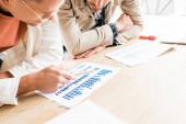 oříznutý pohled na dva mladé podnikatele analyzující dokumenty s grafy a grafy při společné práci na spouštěcím projektu v kanceláři