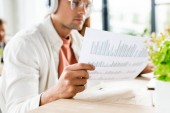 selective focus of young businessman sitting in headphones and analyzing paper with graphs and charts