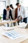 Fotografie selective focus of paper with graphs and charts on desk near businesspeople standing at workplace in office
