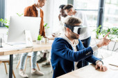 Photo young businessman using vr headset and touching something with finger while multicultural colleagues working in office