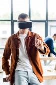 junger Geschäftsmann berührt etwas mit dem Finger, während er Virtual-Reality-Headset im Büro benutzt