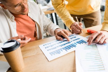 young businesspeople analyzing graphs and charts at workplace in office