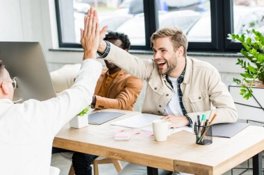 young, cheerful businessmen giving high five while sitting at workplace in office