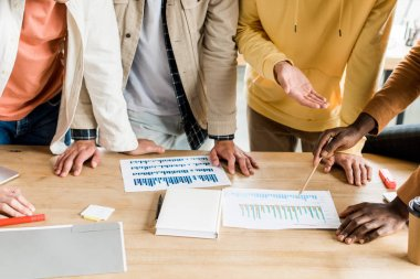 Cropped view of four multicultural businesspeople analyzing papers with graphs and charts while working on startup project together in office stock vector