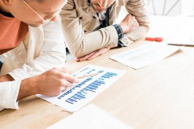 Cropped view of two young businessmen analyzing documents with graphs and charts while working on startup project together in office stock vector