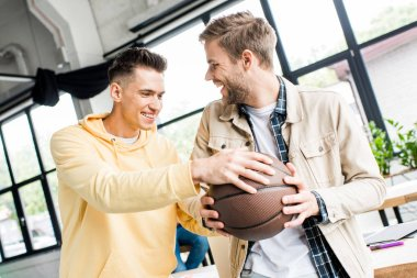 young cheerful businessman taking volleyball from hands of smiling colleague in office