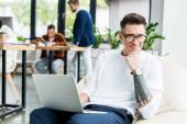 mladý podnikatel v brýlích pomocí notebooku a s úsměvem na kameru v blízkosti kolegů pracující v kanceláři