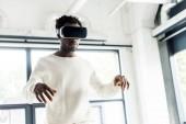 junger afrikanisch-amerikanischer Geschäftsmann mit Virtual-Reality-Headset im Büro