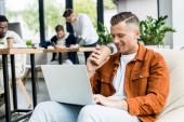 junger Geschäftsmann trinkt Coffee to go und benutzt Laptop, während er im Büro in der Nähe multikultureller Kollegen arbeitet