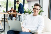 young businessman using laptop and smiling at camera while working near colleagues in office