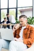 junger Geschäftsmann trinkt Coffee to go und benutzt Laptop, während er in der Nähe von Kollegen im Büro arbeitet