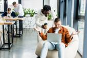 africký americký podnikatel drží kávu jít, zatímco stojí poblíž kolegy pomocí notebooku a ukazuje pokrčení rameny gesto