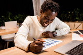 happy african american businessman looking at graphs and charts while working at night in office