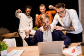felice multiculturale uomini daffari mostrando gesto vincitore durante il lavoro di notte in ufficio