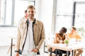 fiatal jóképű üzletember mosolyog a kamera előtt, miközben multikulturális kollégák közelében áll az irodában