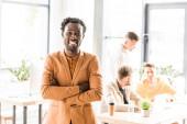 veselý africký americký podnikatel stojící se zkříženýma rukama a usmívající se na kameru