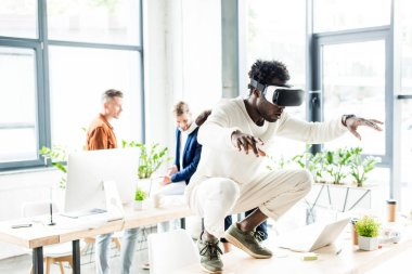 African american businessman squatting on table while using vr headset, and colleagues working in office stock vector