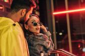 back view of boyfriend kissing attractive girlfriend in sunglasses in night city