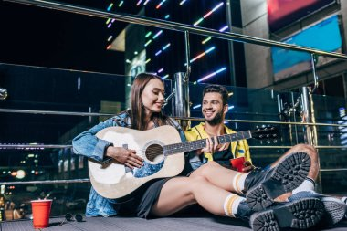 handsome boyfriend with plastic cup and attractive girlfriend playing acoustic guitar in night city