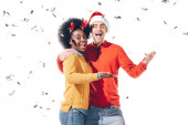 happy interracial couple in santa hat and deer horns celebrating with confetti, isolated on white