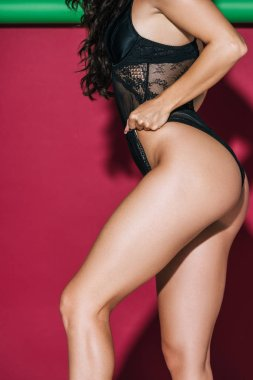 cropped view of girl in black lace lingerie posing on red and green background