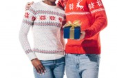 cropped view of interracial couple in winter sweaters holding christmas present, isolated on white