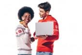 lächelndes gemischtrassiges Paar mit Laptop und Kreditkarte, isoliert auf weiß