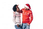 usmívající se mezirasový pár v Santa klobouku a vánoční jelení rohy, izolované na bílém