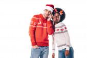 Fotografie šťastný mezirasový pár v Santa klobouku a jelení rohy mluví na smartphonu, izolované na bílém