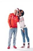 Multikulturelles Paar mit Weihnachtsmann und Hirschhörnern im Smartphone-Gespräch, isoliert auf weiß