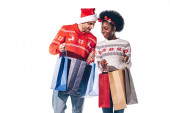 happy interracial couple in santa hat and deer horns holding shopping bags, isolated on white