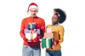 happy interracial couple in santa hat and deer horns holding christmas presents, isolated on white