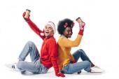 Lächelndes multiethnisches Paar mit Weihnachtsmann und Hirschhörnern, Kaffee to go in der Hand, isoliert auf weiß