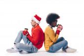 šťastný mezirasový pár v Santa klobouku a jelení rohy drží kávu jít, izolované na bílém