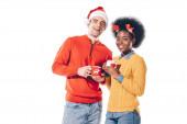 Fotografie multietnický pár v santa klobouku a jelení rohy pití kávy, izolované na bílém