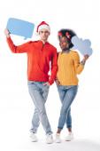 Fotografie interracial pár v Santa klobouku a jeleni rohy držení myšlenkové bubliny a řečové bubliny, izolované na bílém