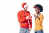 usmívající se multikulturní pár v santa klobouku a jelení rohy držící šálky kávy, izolované na bílém